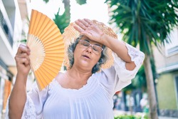 Middle age woman with grey hair using handfan on a very hot day of a heat wave