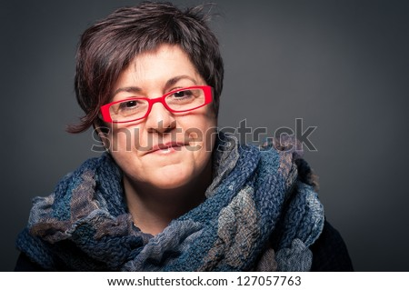 Middle age woman with red glasses close up portrait on dark background.