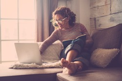 middle age woman working at home sit on the sofa using a laptop. Barefoot relax with backlight atmosphere.