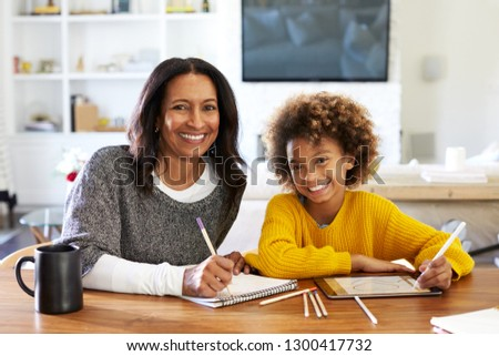 Middle aged African American woman sitting at table in her dining room drawing with her pre-teen granddaughter, smiling to camera, front view, close up