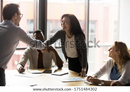 Middle-aged asian korean ethnicity businesswoman shake hands with european millennial client. In modern board room group meeting team leaders greeting each other handshaking showing trust and respect