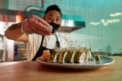 Middle aged asian man preparing sushi in restaurant. Masked chef standing in the kitchen and sprinkles sesame seeds on sushi on the table. Healthy food nibble concept in restaurant