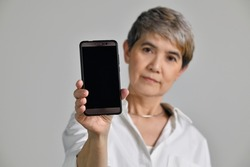 Middle aged Asian woman showing blank smartphone screen while looking at the camera isolated on white background. Focus at a smartphone