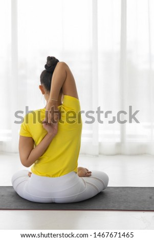 Middle-aged Asian woman wearing sportswear practice yoga on the mat. Put right hand up and attach ear. The left hand rounds back to the other side. Meditate and set breath in and out.