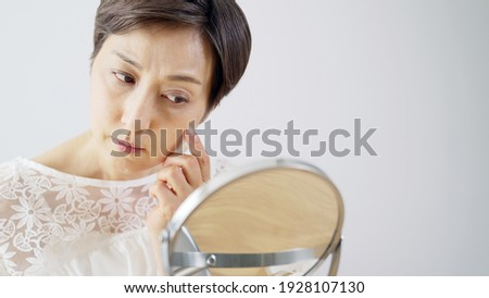 Middle aged Asian woman worrying about her facial skin. Rough skin. Beauty concept. Skin care.