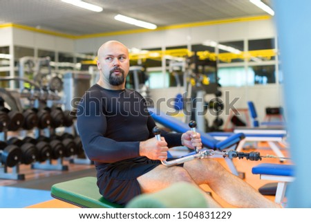 Middle aged athlete doing workouts on a back with power exercise machine in a gym club. Healthy lifestyle and motivation concept.