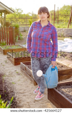 Middle-aged attractive woman doing the watering standing in the vegetable garden amongst raised beds holding a watering can #425664127