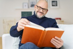 Middle-aged bald man with a goatee wearing glasses sitting on a comfortable couch enjoying a good book with a smile of pleasure