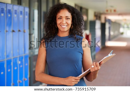 Middle aged black female teacher smiling in school corridor #735915709