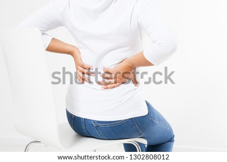 middle aged black woman suffering from backache on chair