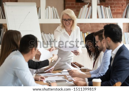 Middle-aged boss giving business paper financial report to diverse employees or clients business partners at office group meeting, company leader and staff do paperwork at corporate briefing concept