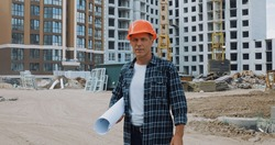 middle aged builder holding blueprint and standing on construction site
