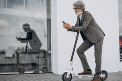 Middle aged business man riding scooter in a classy suit