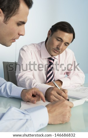 Middle aged businessman discussing over document with male colleague at desk in office