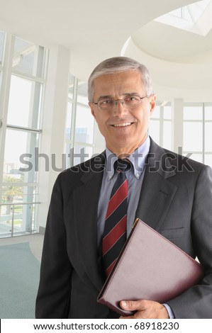 Middle aged businessman in modern office building with leather folder under his arm