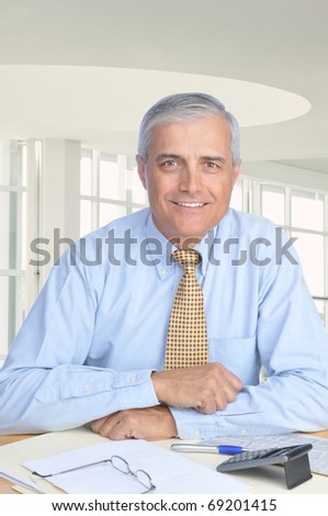 Middle aged Businessman Seated at His Desk in Modern Office Setting. Man is wearing a blue dress shirt and yellow tie with no jacket. Vertical format
