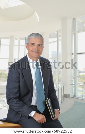 Middle aged businessman sitting on the corner of his desk holding a folder. Vertical format in a modern office building.