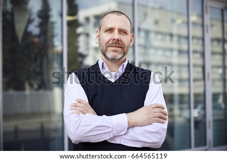 Middle aged businessman standing in front of his office. #664565119