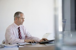 Middle aged businessman using computer at office desk