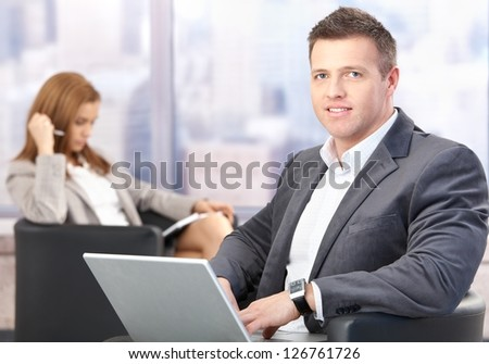 Middle-aged businessman using laptop, sitting in office lobby, having conference break, smiling.