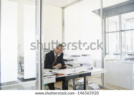 Middle aged businessman using telephone and calculator at office desk