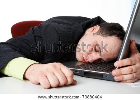 Middle aged businessman with his head on keyboard of laptop sleeping