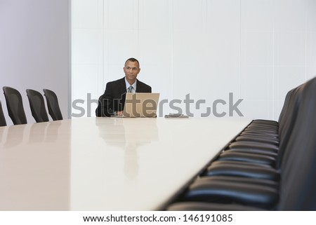 Middle aged businessman with laptop in board room