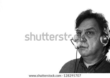 middle-aged businessman works in headphones with microphone behind computer, black and white