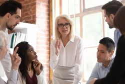 Middle aged businesswoman boss team leader defines tasks and corporate goals aims for multinational employees staff at meeting in office, mentoring brainstorming lead by older company member concept