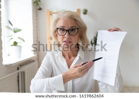 Middle-aged businesswoman giving online presentation discuss contract details with partner or client giving consultation distantly looks at camera, make video call, conferencing with advisor concept