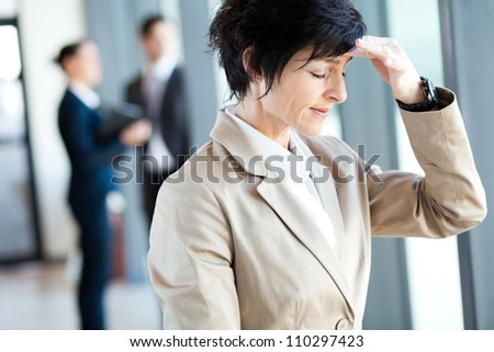 middle aged businesswoman having headache in office