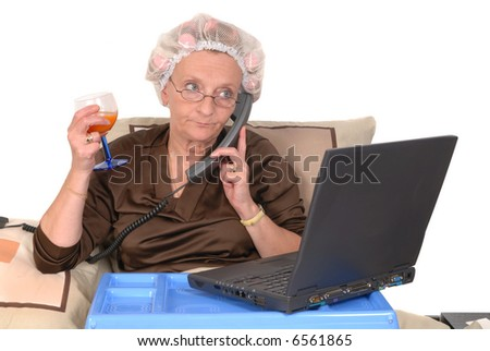 Middle aged businesswoman in bed, laptop on tray, making a phone call.  Glass of fruit juice in right hand