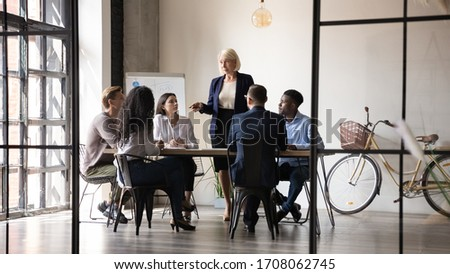 Middle-aged businesswoman lead meeting with multicultural businesspeople in office brainstorm together, confident mature female boss speak talk at briefing with employees, leadership concept
