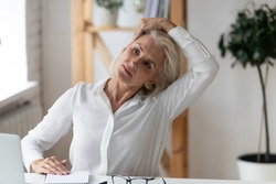 Middle-aged businesswoman sit at office workplace do gymnastics exercise turn head reduces tiredness, numb muscles, raises enthusiasm, improves concentration, increases productivity at workday concept