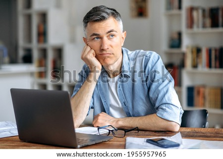 Middle aged caucasian business man or freelancer sitting at workplace, working on laptop, resting head on hand because of tired, doing work overtime, stressed and bored, need rest, pensive looks away Photo stock ©