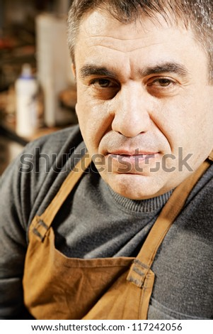 Middle-aged caucasian man in apron closeup photo