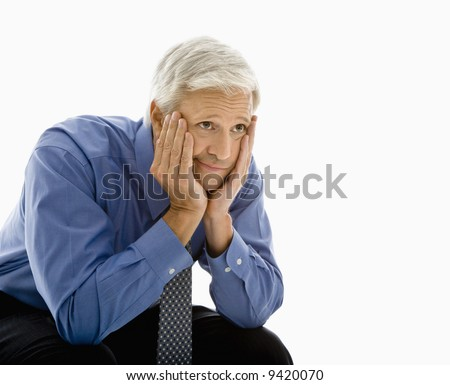 Middle aged Caucasian man with head resting in hands looking bored.