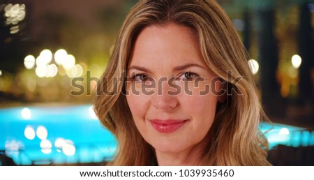 Middle aged Caucasian woman outside at hotel pool smiling at the camera #1039935460