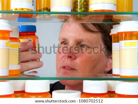 Middle aged caucasian woman reading medication label on prescription bottle in medicine cabinet, view from inside of med cabinet. Concept of wellness, overwhelming management of medications. #1080702512