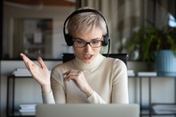 Middle-aged Caucasian woman sit at desk in headphones consult client on laptop online, young businesswoman wearing headset work on computer, talk with business partner using webcam