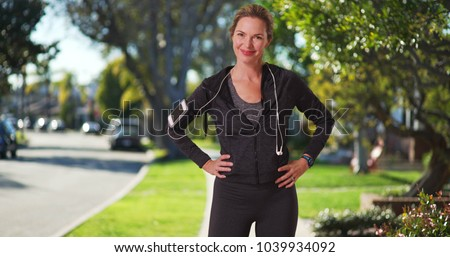 Middle aged Caucasian woman smiling at camera in sunny neighborhood post workout