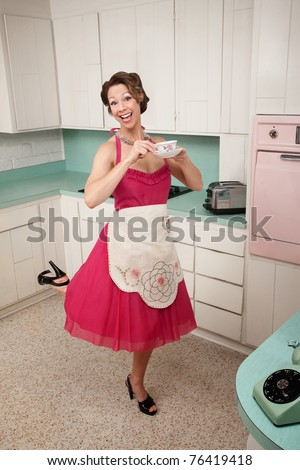 Middle-aged Caucasian woman standing on one foot in kitchen