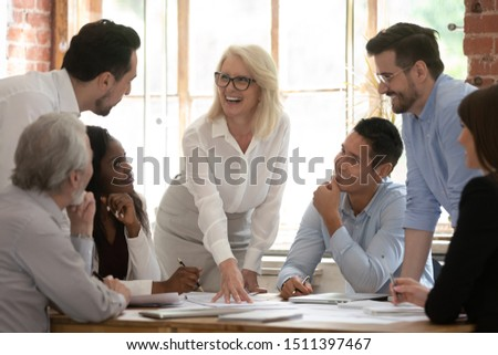 Middle aged company boss and diverse corporate staff at meeting in boardroom, people discuss paperwork sales growth, executive manager provide documents with statistics to client or investor concept