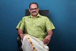 Middle aged confident man wearing traditional Kerala dress sitting on a chair