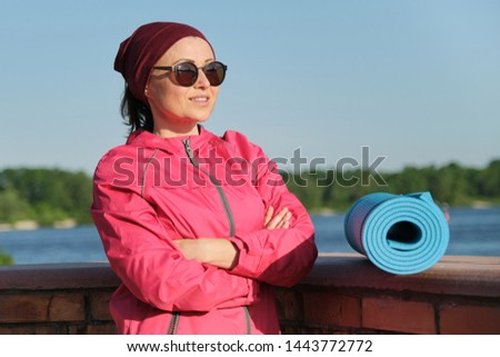 Middle-aged confident sports woman with yoga mat and bottle of water with crossed folded arms, an outdoor evening sunny park near the river. Active healthy lifestyle of an age female #1443772772