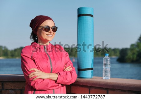 Middle-aged confident sports woman with yoga mat and bottle of water with crossed folded arms, an outdoor evening sunny park near the river. Active healthy lifestyle of an age female
