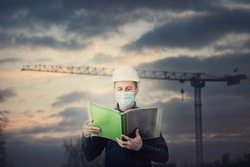 Middle aged contractor or architect holding a document folder, wearing protective helmet and face mask as Covid-19 prevention. Engineer with hardhat over construction site background with tower crane