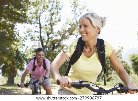 Middle Aged Couple Cycling Through Countryside Stock photo ©