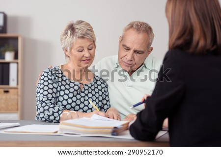 Middle Aged Couple Discussing Something on the Document to a Female Agent at the Table. - Shutterstock ID 290952170