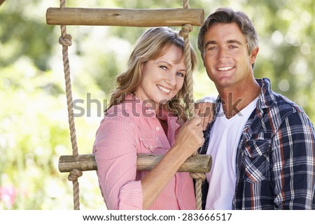 Middle Aged Couple In Garden By Treehouse Stock photo ©